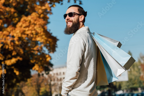 Papier Peint - Man fashion style. Bearded hipster guy with shopping bags enjoying autumn sunny day. Blur fall trees and blue sky background.