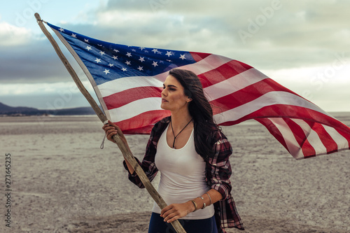 Papier Peint - Woman holding a USA flag on the beach