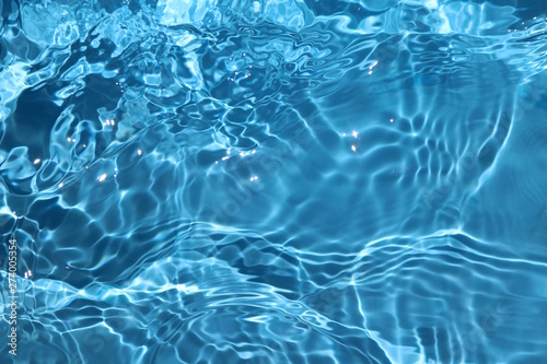 Papier Peint - Blue and bright water surface with sun refection in swimming pool for background