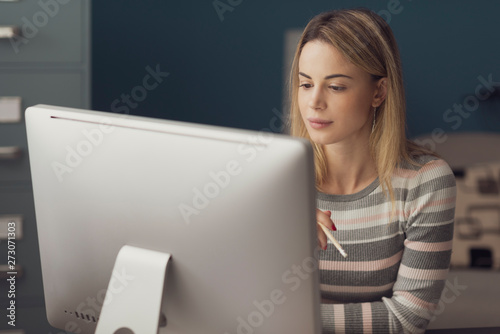 Papier Peint - Young attractive woman working with a computer