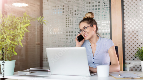 Papier Peint - Young business woman working on laptop in office